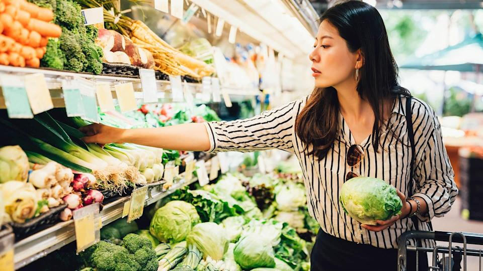 asian local woman buy vegetables and fruits in supermarket. young chinese lady holding green leaf vegetable and picking choosing green onion on cold open refrigerator. elegant female grocery shopping - Image