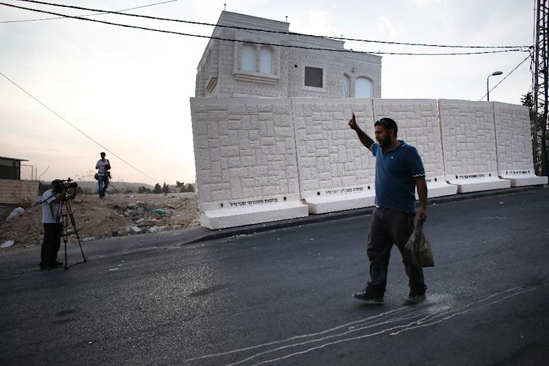 A television crew films as a Palestinian man walks past a wall put in place by Israeli officials to separate the Palestinian neighborhood of Jabel Mukaber from the Jewish settlement of Armon Hanatziv in east Jerusalem, on October 18, 2015