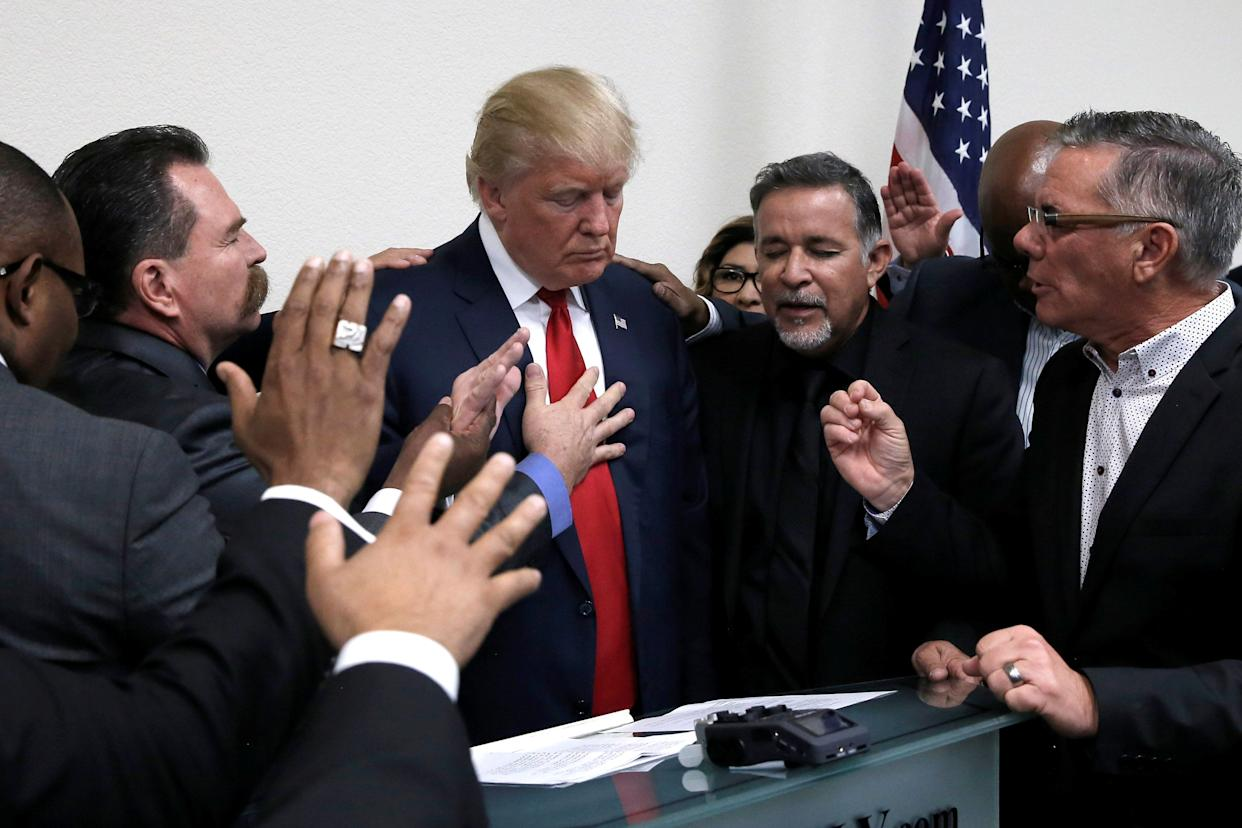 Republican presidential nominee Donald Trump prays with pastors during a campaign visit to the International Church of Las Vegas and the International Christian Academy in Las Vegas, Nevada, U.S., October 5, 2016.