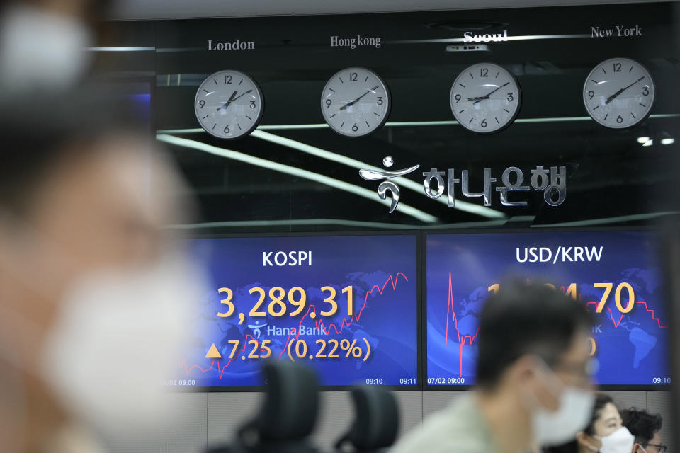 Currency traders watch computer monitors near screens showing the Korea Composite Stock Price Index (KOSPI), left, and the foreign exchange rate between U.S. dollar and South Korean won at a foreign exchange dealing room in Seoul, South Korea, Friday, July 2, 2021. Shares were mostly higher in Asia on Friday, though markets in Shanghai and Hong Kong declined a day after the Chinese Communist Party marked its centenary with tough talk by Chinese President Xi Jinping. (AP Photo/Lee Jin-man)