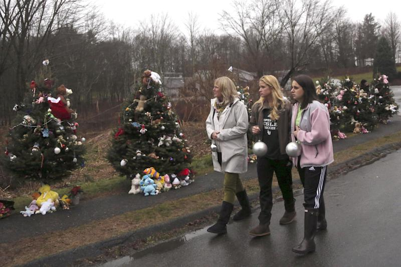 FILE - In this Monday, Dec. 17, 2012 file photo, mourners carry ornaments to decorate the Christmas trees at one of the makeshift memorials for the Sandy Hook Elementary School shooting victims, in Newtown, Conn. In the wake of the shooting, the grieving town is trying to find meaning in Christmas. (AP Photo/Mary Altaffer, File)
