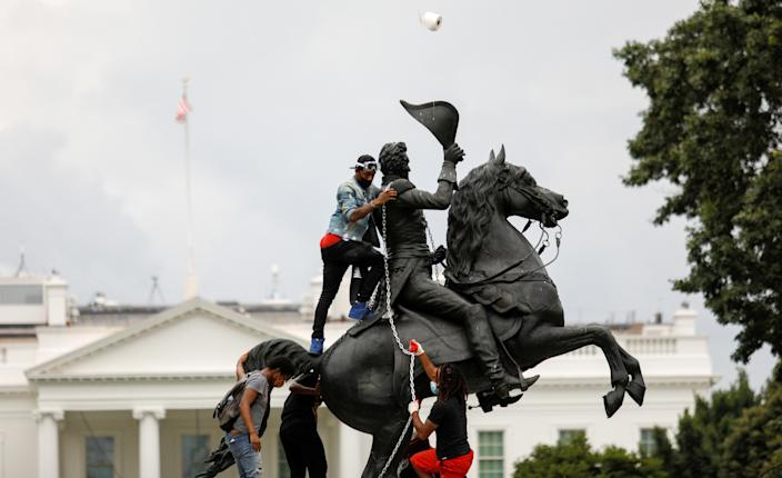 Protestors attach a chain to the statue of U.S. President Andrew Jackson in the middle of Lafayette Park in front of the White House in an attempt to pull it down as someone throws a roll of toilet paper at the statue during racial inequality protests in Washington, D.C., U.S., June 22, 2020. (Tom Brenner/Reuters)