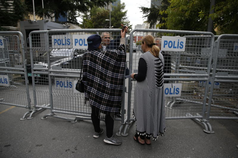 Civilians wait to enter a blocked road leading to the Saudi Arabia consulate in Istanbul, Tuesday, Oct. 9, 2018. Saudi journalist Jamal Khashoggi disappeared a week ago after entering Saudi Arabia's consulate to obtain paperwork required for his marriage to his Turkish fiancee. Turkish officials have alleged he was killed in the compound while Saudis officials said he left the building unharmed. (AP Photo/Lefteris Pitarakis)