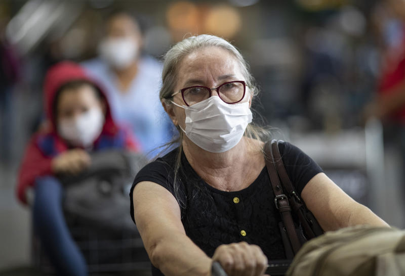Passengers wear masks as a precaution against the spread of the new coronavirus COVID-19 as they arrive to the Sao Paulo International Airport in Sao Paulo, Brazil, Thursday, Feb. 27, 2020. (AP Photo/Andre Penner)