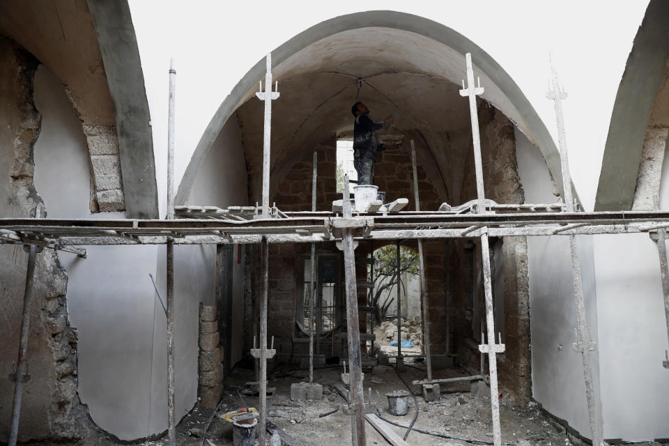 A worker renovates the long-abandoned 200-year-old Ghussein palace, in the old quarter of Gaza City, Monday, Dec. 14, 2020. Less than 200 of these old houses are still partly or entirely standing, according to officials and they are threatened by neglect, decaying and urban sprawl. (AP Photo/Adel Hana)