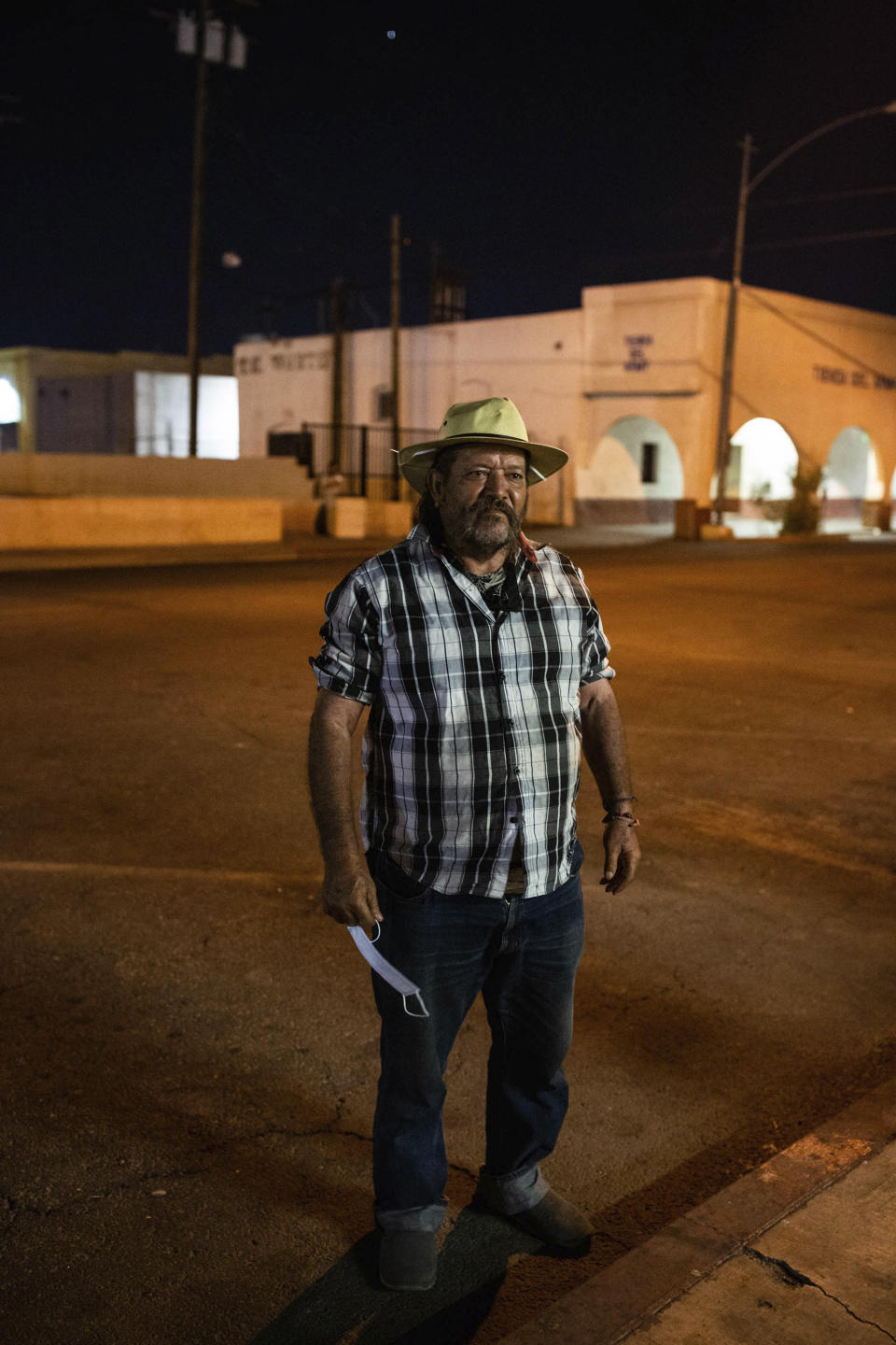 Sergio Gomes Macias stands on street in Calexico, Calif., on July 23, 2020. Macias is a farmworker who sleeps on the street about 500 feet from the Mexican border. He says the pandemic has made it hard to find food, water and restrooms since nonessential businesses closed amid high infection rates in the area. Many homeless people work low-wage essential jobs on the front lines of the pandemic, putting them at higher risk of catching and possibly transmitting the virus. Many who work with these communities are reluctant to speak about this risk for fear of further stigmatizing homeless people, even though they do the front-line jobs others can avoid. (Anna Maria Barry-Jester/KHN and the Howard Center For Investigative Journalism via AP)
