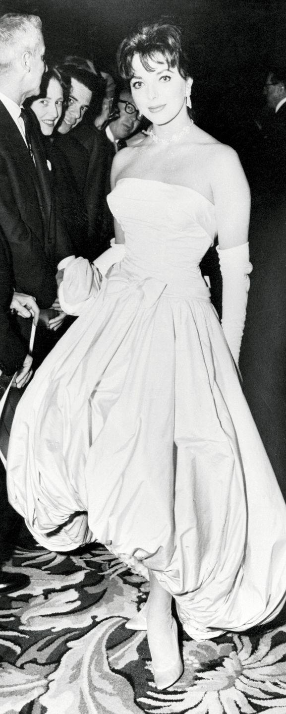 <p>Joan Collins clearly turned heads in this bubble hem gown—and in the '50s no formal look was complete without elbow-length gloves. </p>
