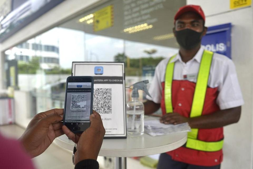 A customer checks-in using the MySejahtera app before entering a petrol station in Setia Alam November 10, 2020. ― Picture by Miera Zulyana