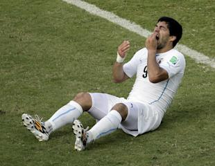 Luis Suarez grabs his tooth in apparent pain after biting Italy's Giorgio Cheillini. (AP)