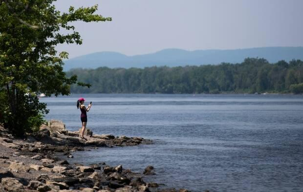 A person takes a photo from the shores of the Ottawa River in Ottawa on June 6, 2021, amidst both the COVID-19 pandemic and an early June heat wave. (Justin Tang/The Canadian Press - image credit)