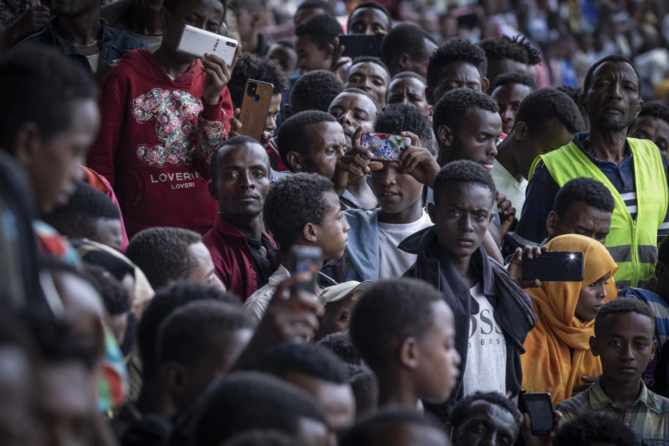 Supporters in the stands take pictures with their smartphones at the final campaign rally of Ethiopia's Prime Minister Abiy Ahmed, in the town of Jimma in the southwestern Oromia Region of Ethiopia Wednesday, June 16, 2021. The country is due to vote in a general election on Monday, June, 21, 2021. (AP Photo/Mulugeta Ayene)