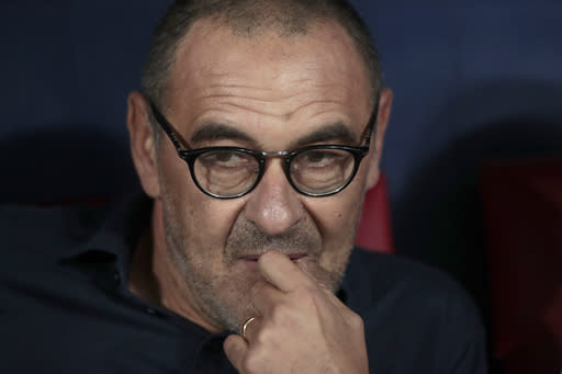 FILE - In this Wednesday, Sept. 18, 2019 filer, Juventus' head coach Maurizio Sarri takes his seat on the bench prior to the Champions League Group D soccer match between Atletico Madrid and Juventus at the Wanda Metropolitano stadium in Madrid, Spain. Cristiano Ronaldo scored twice but could not prevent Juventus from going out of the Champions League despite a 2-1 victory over Lyon in its rearranged second-leg match Friday. The French team progressed to the quarterfinals on away goals after a 2-2 draw on aggregate. (AP Photo/Bernat Armangue, File)
