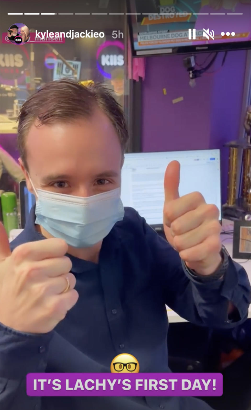 Beauty and the Geek star Lachy Mansell wears a face mask and gives a thumbs up from his desk at his new job on KIIS FM's The Kyle & Jackie O Show