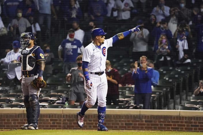 Chicago Cubs' Javier Baez gestures as he crosses home plate after hitting a home run against the Milwaukee Brewers during the fourth inning of a baseball game, Monday, April 5, 2021, in Chicago. (AP Photo/David Banks)