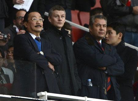 Cardiff City's owner Vincent Tan (L) and Ole Gunnar Solskjaer (C) are seen in the director's box before their English Premier League soccer match against Arsenal at the Emirates Stadium in London January 1, 2014. REUTERS/Dylan Martinez