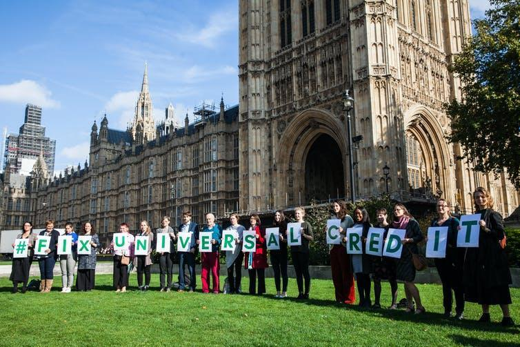 Protesters outside parliament hold up signs spelling 'FIX UNIVERSAL CREDIT'