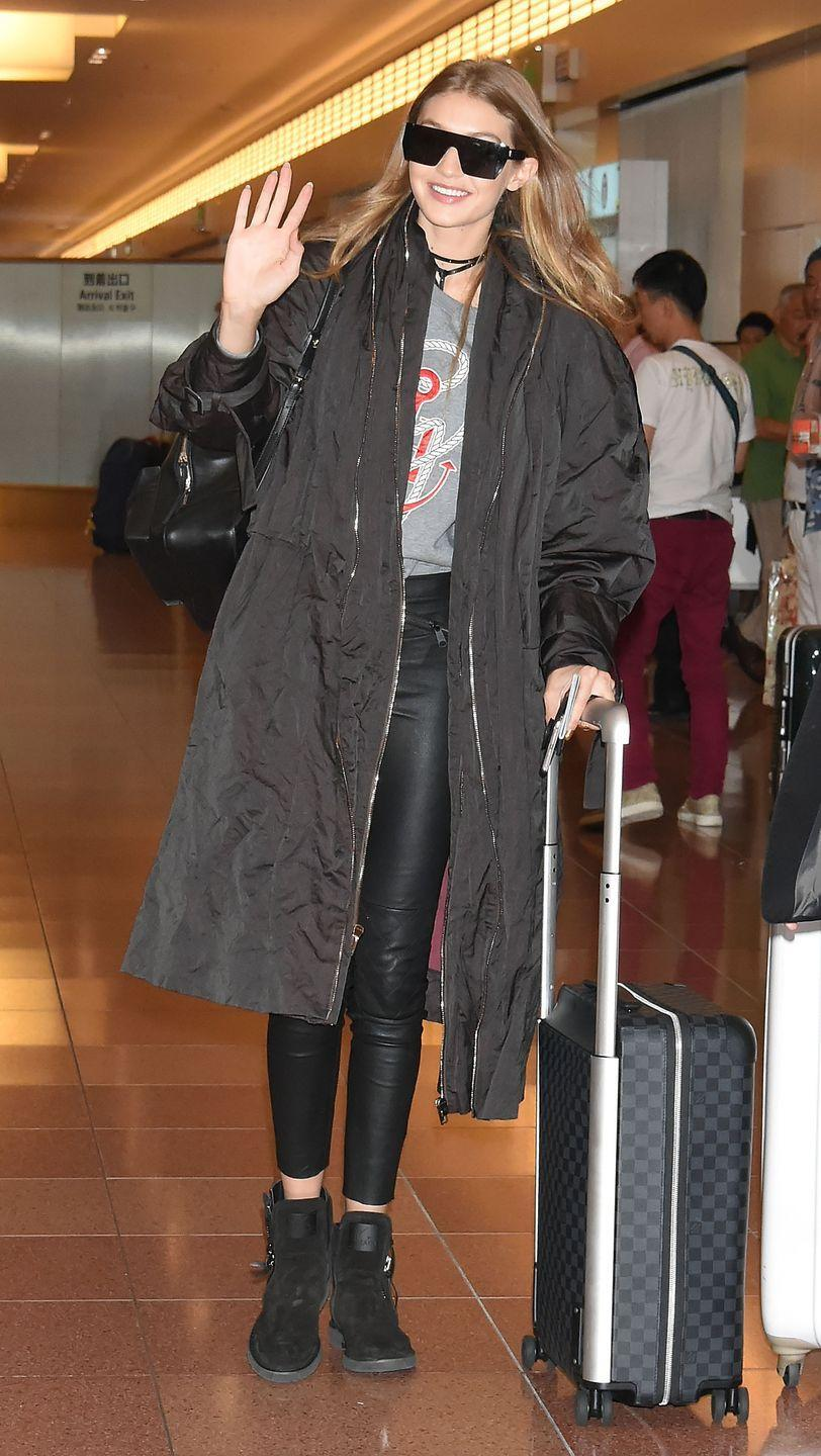 <p>In a Tommy x Gigi graphic sweater, dark trench coat, quilted leather leggings, suede booties, a studded wrap choker and futuristic Max Mara sunglasses while arriving in Tokyo. She packed up a leather backpack and a checkered luggage for the trip.</p>