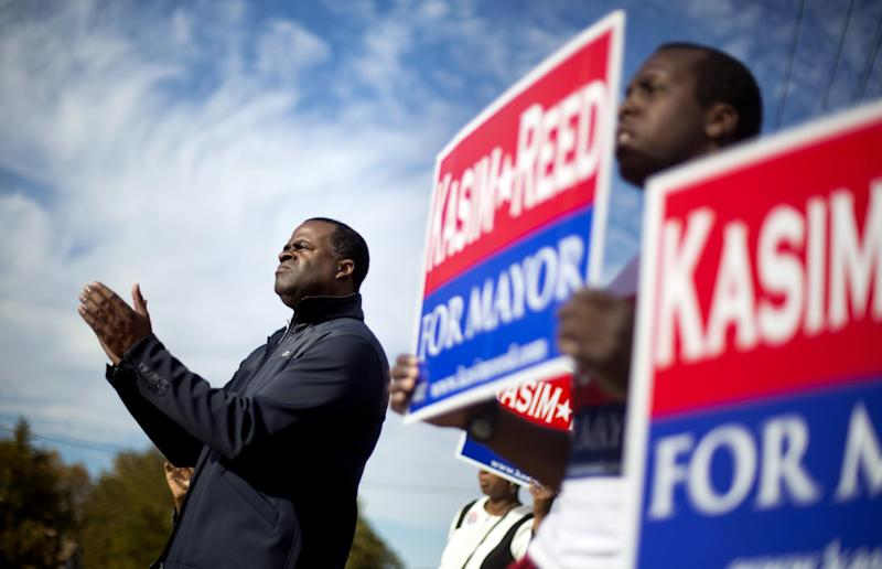 Atlanta Mayor Kasim Reed, left, claps along to a song as he campaigns at an intersection in west Atlanta, Tuesday, Nov. 5, 2013. Voters will head to the polls Tuesday to decide whether Mayor Reed will be elected a second term. (AP Photo/David Goldman)