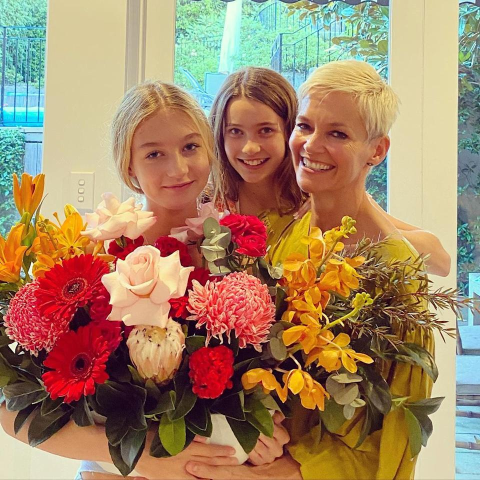 Jessica Rowe and her daughters, Allegra, 14, and 12-year-old Giselle, pose with a large bunch of flowers