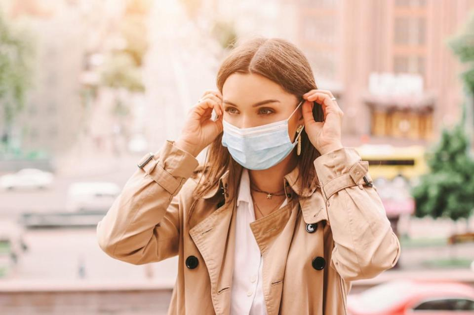 girl wear medical face mask on sunny city street