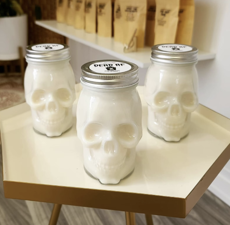 three white Skull Candles in jars sitting on white hexagon table