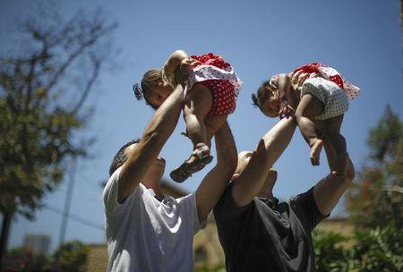 Jason Howe, 48, and Adrian Perez (L), 48, who were married in Spain, and again in California, hold their one-year-old twin daughters Clara (R) and Olivia at a playground in West Hollywood, California after the United States Supreme court ruled on California's Proposition 8 and the federal Defense of Marriage Act, June 26, 2013. REUTERS/Lucy Nicholson