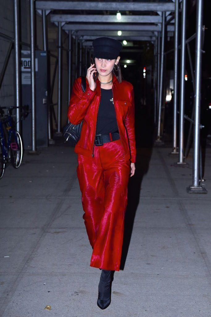 <p>In a shiny red, '90s-inspired suit, with black boots and a black hat, while out in New York.</p>