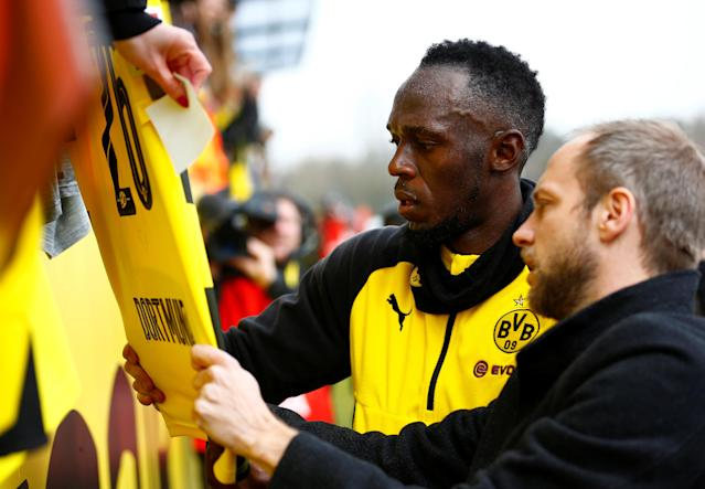Soccer Football - Usain Bolt participates in a training session with Borussia Dortmund - Strobelallee Training Centre, Dortmund, Germany - March 23, 2018 Usain Bolt signs a shirt after Borussia Dortmund training REUTERS/Thilo Schmuelgen
