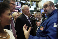 FILE - In this Wednesday, July 25, 2018 file photo, Specialist Peter Giacchi, right, talks with Bloom Energy board member Colin Powell, center, and company officials on the floor of the New York Stock Exchange during their IPO. Powell has consistently defended his support of the Iraq War. But the lifelong Republican had little use for Trump, endorsing Hillary Clinton in 2016 and speaking in support of Biden at the 2020 Democratic convention. He left the Republican party after the Jan. 6 assault on the Capitol. (AP Photo/Richard Drew, File)