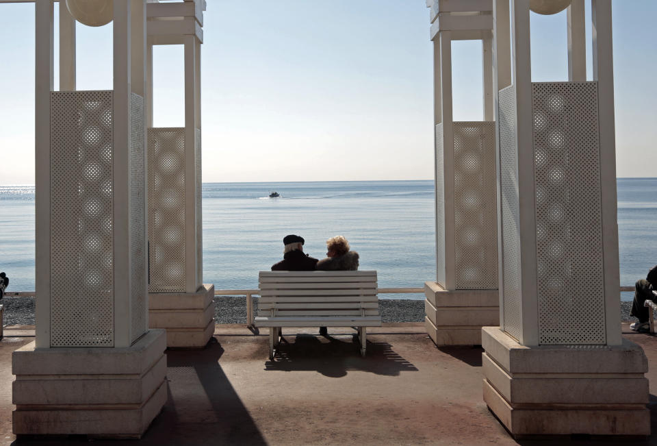 Elderly people sit on a bench in Nice, France