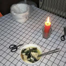 This photo provided by Zhong Hanneng shows a candle she lit in memory of her son, Peng Yi, during a meal of noodles at her home in Wuhan, China, in July 2020. Peng first started coughing on Jan. 23 at the beginning of the coronavirus outbreak, but because of a shortage of test kits, he wasn't able to get tested for days. His first test result came out negative, barring him access to a hospital bed, and he wasn't able to be hospitalized until weeks later. By then his condition was critical, and he passed away on Feb. 19. (Zhong Hanneng via AP)