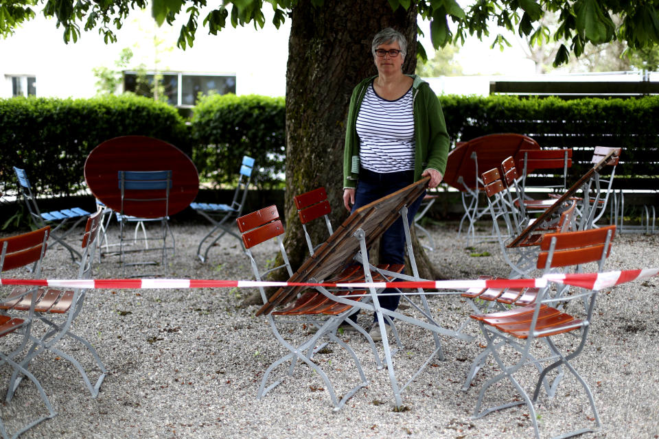 In this photo taken Friday, May 1, 2020 brewery daughter Sabine Detter stands behind barrier tape in the closed beer garden in her 120 year old family brewery and traditional Bavarian restaurant in Altoetting, Germany. The 'Graminger Weissbraeu' brewery, which has been in the same family for a century, is preparing to welcome guests back to its restaurant for the first time in two months — with new rules and fears for the future. (AP Photo/Matthias Schrader)