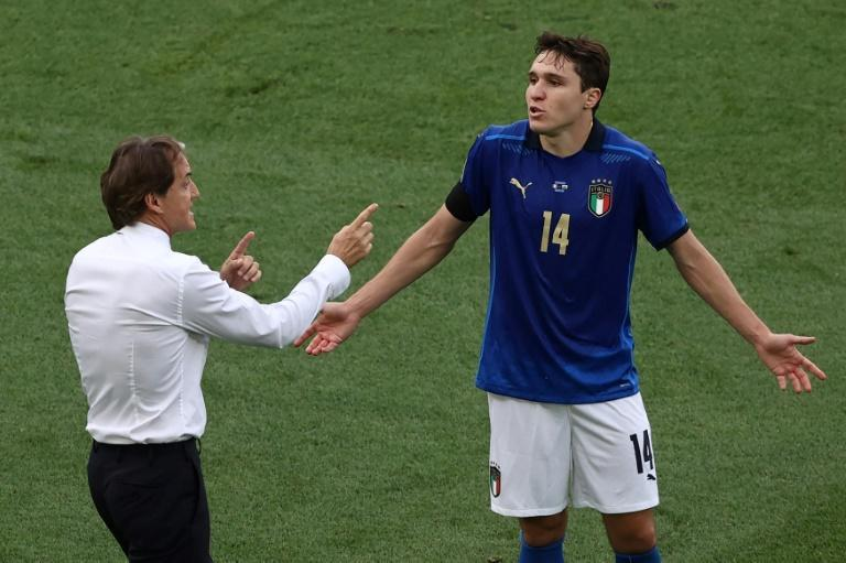 Italy coach Roberto Mancini (L) gives instructions to midfielder Federico Chiesa.