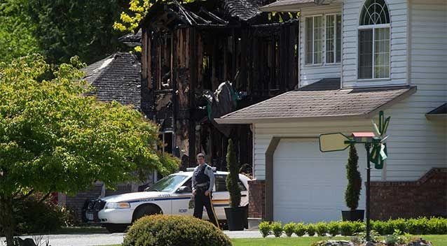 An RCMP officer stands in front of a burned home during the investigation of multiple homicides in Rosedale, British Columbia, Canada, east of Chilliwack. Photo: AP