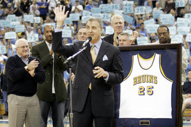 FILE - In this Dec. 18, 2004, file photo, former UCLA basketball player Gail Goodrich, foreground, waves to the crowd during a ceremony retiring his UCLA No. 25 jersey at half time of the UCLA-Michigan game in Los Angeles. More than three decades after the 1988 NBA All-Star weekend in Chicago, some details of the classic slam dunk contest showdown between Michael Jordan and Dominique Wilkins are a bit fuzzy to Hall of Famer Gail Goodrich. One of five judges for the competition, the former Los Angeles Lakers' great is, however, certain of a few things: His Airness soared to a slightly higher level than the Human Highlight Reel, there was no pressure to crown Jordan the slam dunk king on his home court and the judges were not in cahoots.(AP Photo/Francis Specker, File)