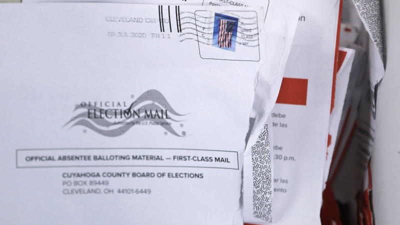 Applications for voter ballots are seen at the Cuyahoga County Board of Elections Tuesday, July 14, 2020, in Cleveland. As more states embrace mail-in balloting, an often overlooked detail has emerged as a partisan dividing line: postage. Questions over whether postage will be required for absentee ballot applications and ballots themselves, who pays for it and what happen to envelopes without stamps are the subject of lawsuits and Statehouse political brawls. (AP Photo/Tony Dejak)