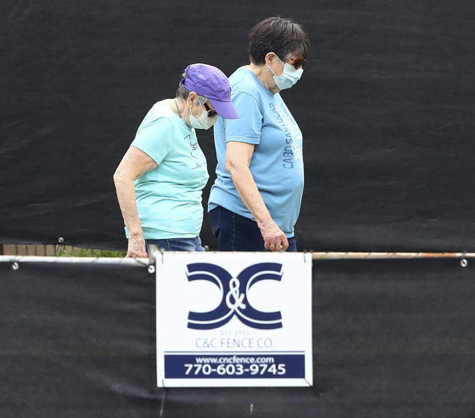 """A pair of women behind a blackened fence where quarantined Grand Princess cruise ship passengers are isolated in a housing area at Dobbins Air Reserve Base on Thursday, March 12, 2020, in Marietta, Ga. """"Prior to arriving here, the passengers were medically screened by the U.S. Department of Health and Human Services and Centers for Disease Control and Prevention,"""" said Col. Craig McPike, Dobbins installation commander. """"The passengers who were asymptomatic were transferred here and other federal military installations for COVID-19 testing and quarantine."""" Should any individuals be identified as ill during their quarantine period, the Department of Health & Human Services, the lead federal agency, has procedures in place to transport them to a local civilian hospital. """"CDC is fully responsible for all aspects of the quarantine operation, and Dobbins personnel will have no contact with these passengers.  (Curtis Compton/Atlanta Journal-Constitution via AP)"""