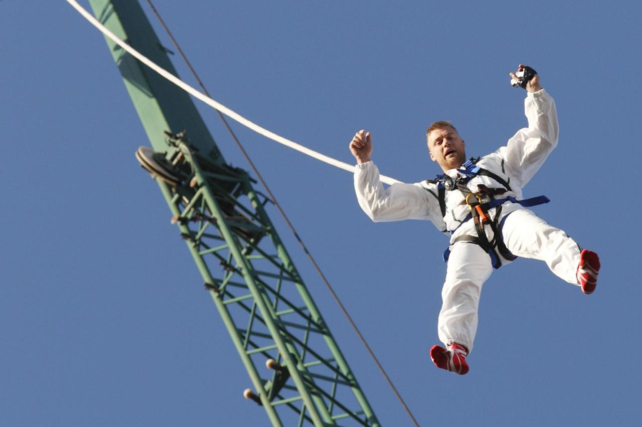 """Former England cricketer Andrew """"Freddie"""" Flintoff dangles from a rope as he attempts to break the world record for the highest reverse bungee jump in North London on March 19, 2012. Flintoff was attempting to set twelve Guinness World Records in 12 hours to raise money for the Sport Relief charity. AFP PHOTO / JUSTIN TALLIS (Photo credit should read JUSTIN TALLIS/AFP/Getty Images)"""