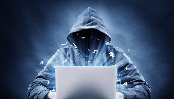 Hooded figure typing on laptop