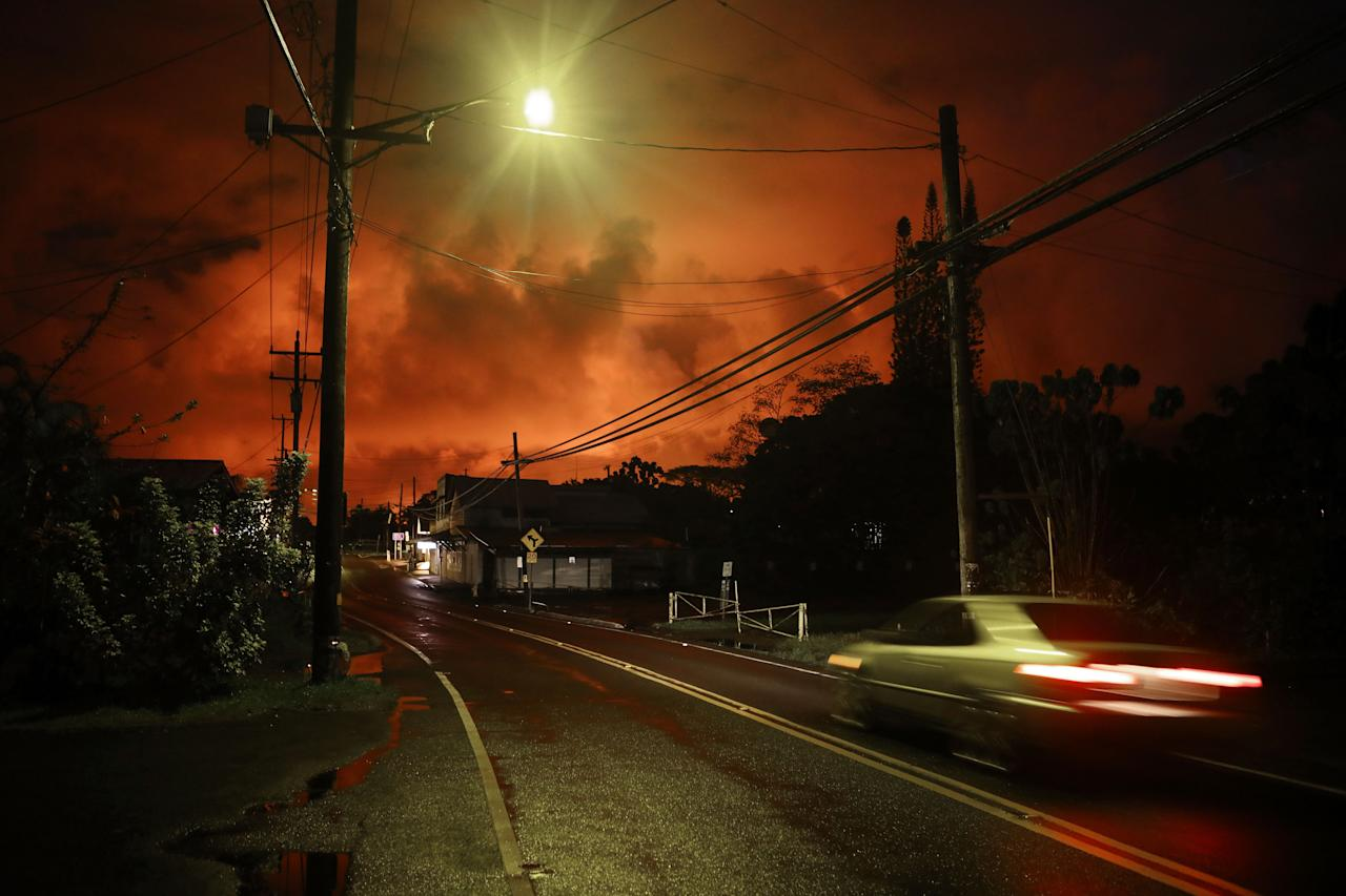 <p>A car passes as lava from a Kilauea volcano fissure illuminates the night sky, after midnight on Hawaii's Big Island, on May 27, 2018 in Pahoa, Hawaii. (Photo: Mario Tama/Getty Images) </p>