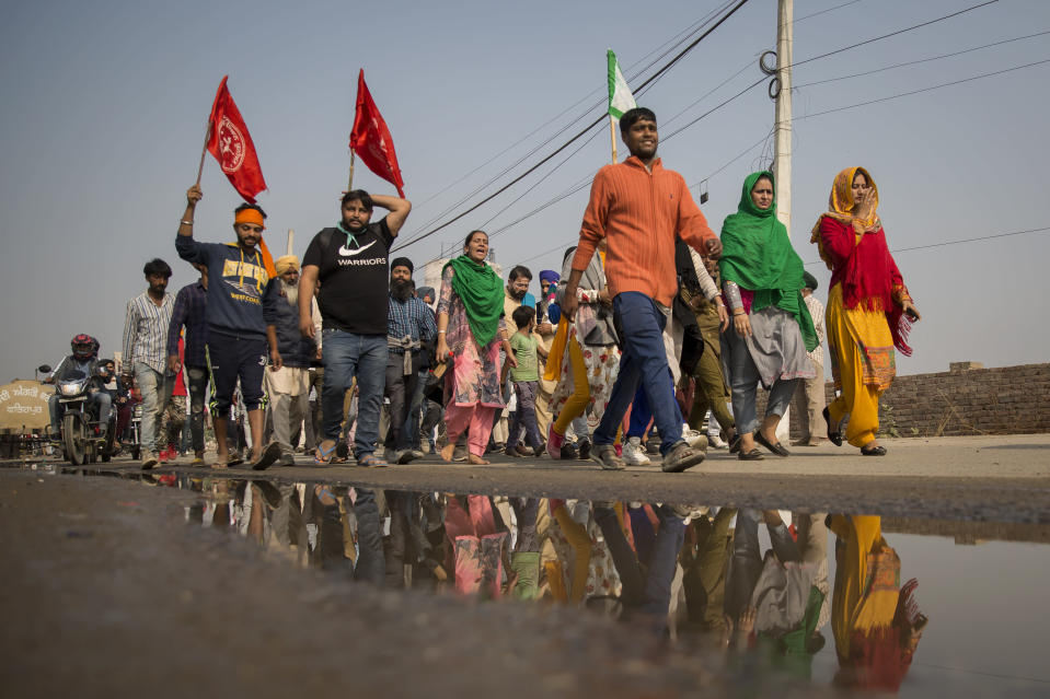 "A group of protesters shout slogans as they arrive to join farmers demanding to abolish new farming laws they say will result in exploitation by corporations, eventually rendering them landless, at the Delhi-Haryana state border, India, Tuesday, Dec. 1, 2020. The busy, nonstop, arterial highways that connect most northern Indian towns to this city of 29 million people, now beat to the rhythm of never-heard-before cries of ""Inquilab Zindabad"" (""Long live the revolution""). Tens and thousands of farmers, with colorful distinctive turbans and long, flowing beards, have descended upon its borders where they commandeer wide swathes of roads. (AP Photo/Altaf Qadri)"