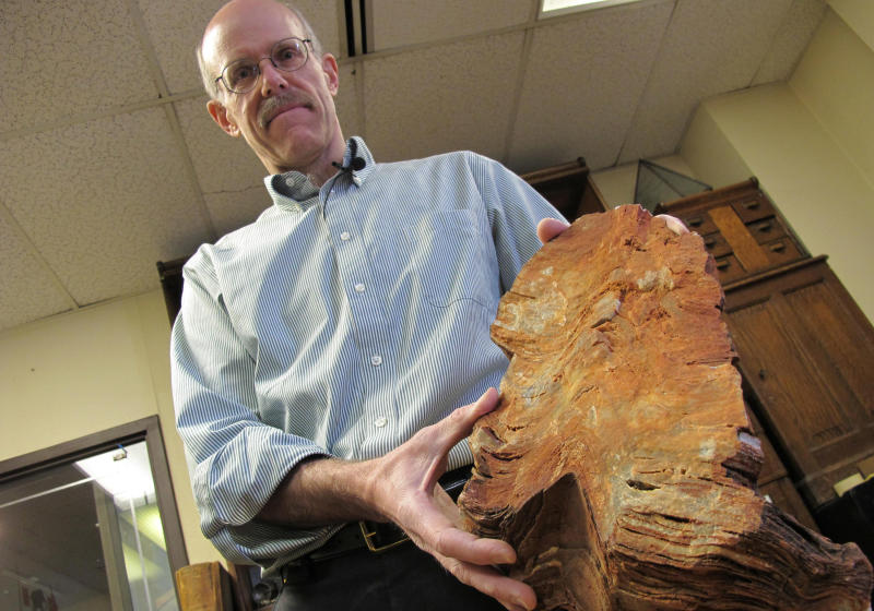 In this Jan. 22, 2013 photo University of Wisconsin-Madison Geoscientist Clark Johnson holds what he says is a 3.5 billion year old rock in Madison, Wis.  Johnson is leading a team of scientists and others studying Earth rocks that are billions of years old looking for crucial information to understand how life might have arisen elsewhere in the universe and guide the search for life on Mars one day.  (AP Photo/Carrie Antlfinger)