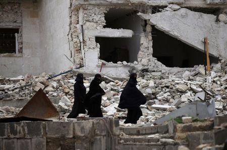Women walk near damaged buildings in the northern Syrian city of al-Bab, Syria March 13, 2017. REUTERS/Khalil Ashawi