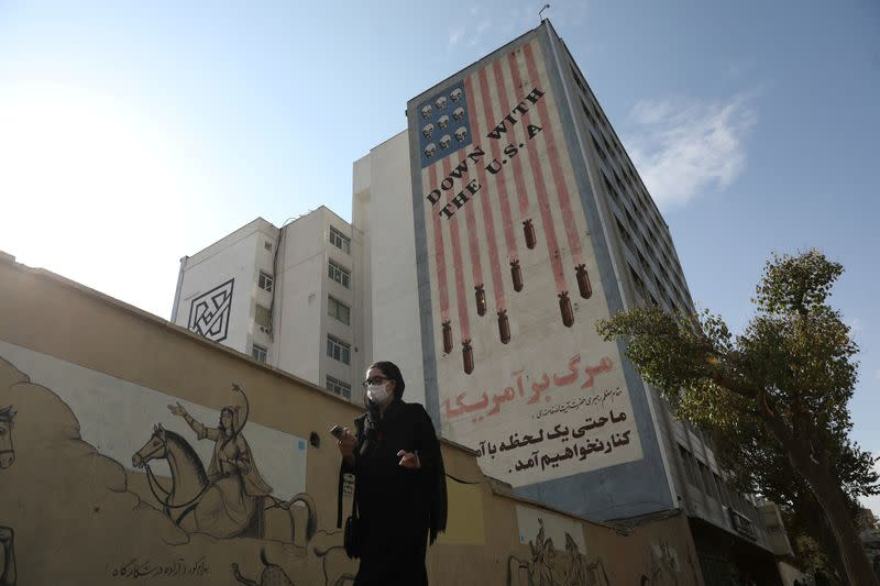 FILE PHOTO: A woman walks as an anti-America image is seen on a building in Tehran
