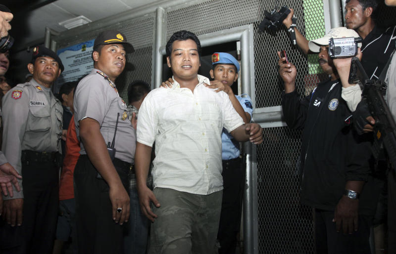 An Indonesian prisoner is escorted by security officers as he is removed from Kerobokan prison in Denpasar, Bali, Indonesia, Thursday, Feb. 23, 2012. Indonesia started moving foreigners and a handful of other inmates from the overcrowded prison on Bali island Thursday after two days of rioting, officials said, as troops backed by water canons and armored vehicles surrounded the tense facility.   (AP Photo/Firdia Lisnawati)