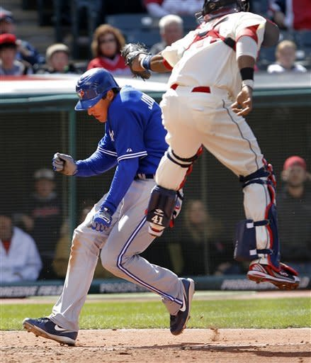 Toronto Blue Jays' Kelly Johnson slips under the tag of Cleveland Indians catcher Carlos Santana to score after a single by Rajai Davis in the eighth inning of a baseball game in Cleveland on Sunday, April 8, 2012. (AP Photo/Amy Sancetta)
