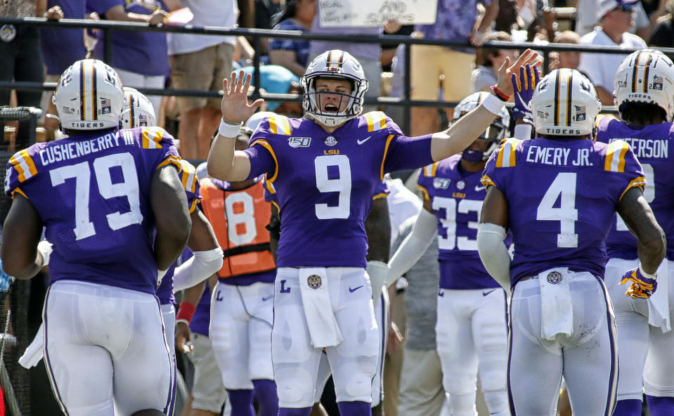 Joe Burrow #9 of the LSU Tigers high-fives teammates after scoring against the Vanderbilt Commodores on Saturday. (Getty)
