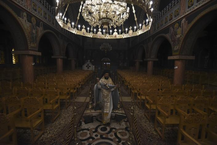 "A Greek Orthodox priest takes part in the Good Saturday ceremony, held without worshippers inside an empty church in the northern city of Thessaloniki, Greece, during a lockdown order by the government to prevent the spread of the coronavirus, on Sunday, April 19, 2020. Greeks celebrated the Resurrection of Christ very differently Saturday night: confined at home, instead of massively congregating in churches. And they had to do without the ""Holly Light"" from Jerusalem, which arrived in Athens but was not distributed, as authorities remained ready to crack down on anyone who violated the strict curfew imposed almost a month ago. (AP Photo/Giannis Papanikos)"