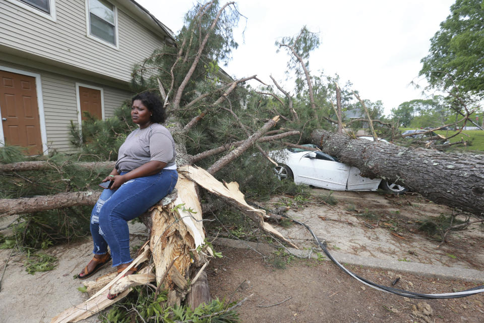 Myesha Gore of Calhoun City, Miss., sits on the trunk of a shattered pine tree Monday, May 3, 2021, as the rest of the tree crushed her car behind her while she was visiting her mother in Vardaman during Sunday's severe weather. (Thomas Wells/The Northeast Mississippi Daily Journal via AP)