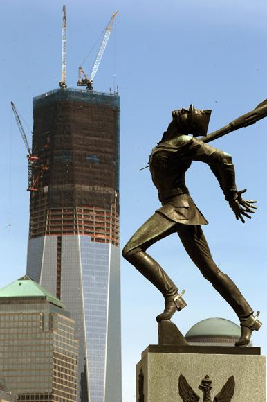 JERSEY CITY, NJ - APRIL 30: The Katyn monument is seen in Exchange Place as construction continues on One World Trade Center (TOP L) after workers moved a steel column into place to make it New York City's tallest building on April 30, 2012 as seen from Jersey City, New Jersey. One World Trade Center's height is now just beyond the 1,250 feet of the observation deck at the Empire State Building.  (Photo by Mario Tama/Getty Images)